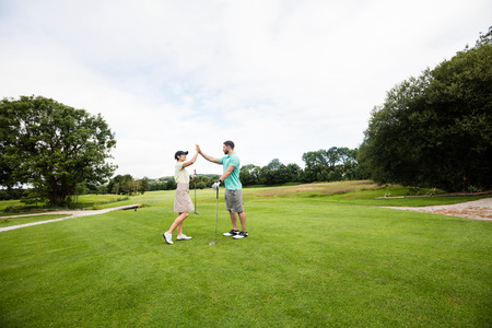 Couple giving high five to each other in golf course