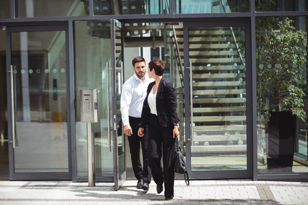 Businesspeople interacting with each other while leaving office