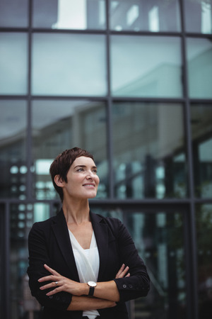 company premises: Smiling businesswoman standing with arms crossed in office premises