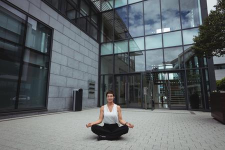 company premises: Businesswoman performing yoga in office premises