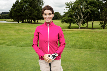 woman golf: Portrait of smiling woman standing with golf club in golf course