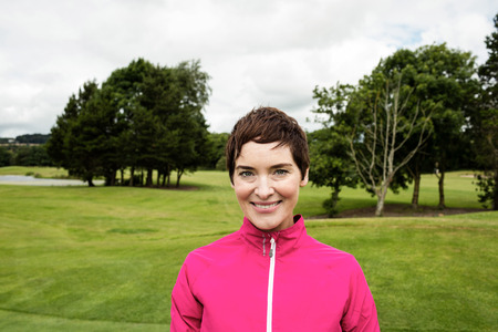 woman golf: Portrait of smiling woman standing in golf course Stock Photo