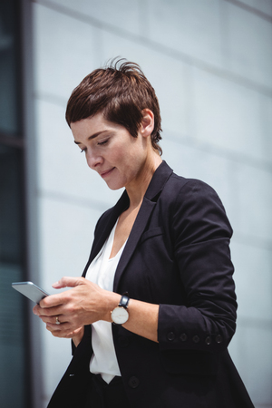 company premises: Businesswoman using mobile phone in office premises