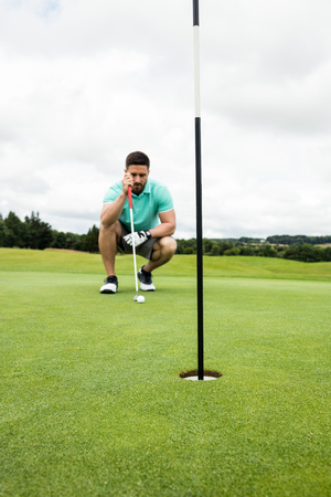 putt: Man squatting to line up his putt in golf course Stock Photo