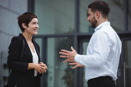 premises: Businesspeople interacting with each other in office premises Stock Photo