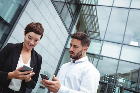company premises: Businesspeople using mobile phone in office premises Stock Photo