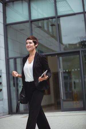 premises: Smiling businesswoman holding digital tablet in office premises