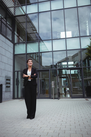 premises: Smiling businesswoman standing with arms crossed in office premises
