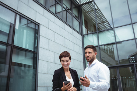 Businesspeople using mobile phone in office premises Stock Photo