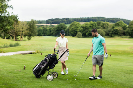 woman golf: Male instructor assisting woman in learning golf at golf course