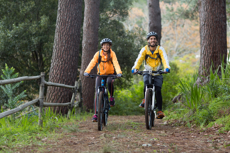 Biker couple cycling in countryside forest