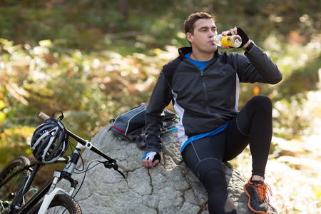 adventuring: Portrait of male biker drinking water in forest at countryside Stock Photo
