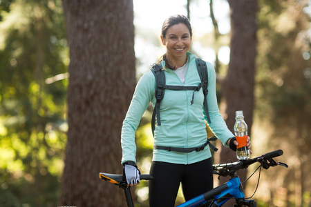 adventuring: Portrait of female biker standing with mountain bike in forest at countryside