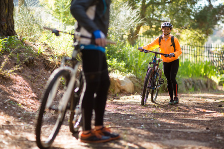 dirt track: Female biker walking with mountain bike on dirt track in countryside
