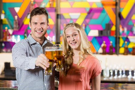 socializando: Retrato de pareja sonriente mostrando un vaso de cerveza en la barra de Foto de archivo