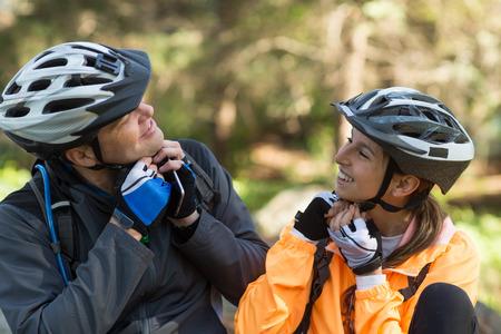 Fietserpaar die fietshelm in bos dragen bij platteland
