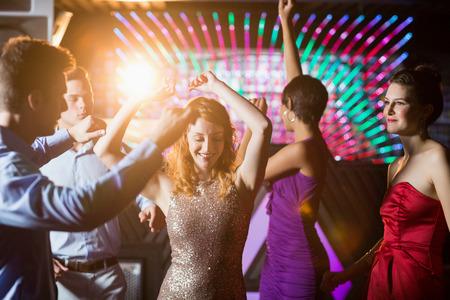 socializando: Grupo de amigos sonrientes que bailan en la pista de baile en la barra de