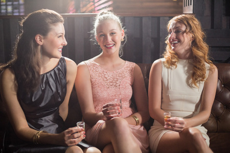 shot glass: Portrait of smiling female friends holding shot glass of tequila in bar