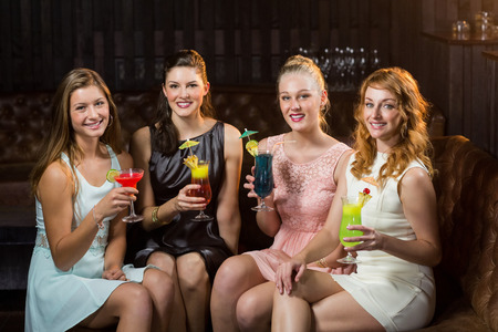 cocktail glasses: Portrait of smiling female friends holding glasses of cocktail in bar