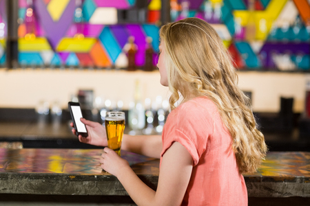 Rear view of beautiful woman using mobile phone while having beer in restaurant