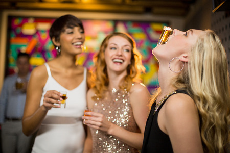 shot glass: Woman balancing a shot glass on her mouth in bar