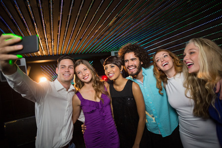 Grupo de amigos sonriendo tomar una autofoto desde el teléfono móvil en la barra de