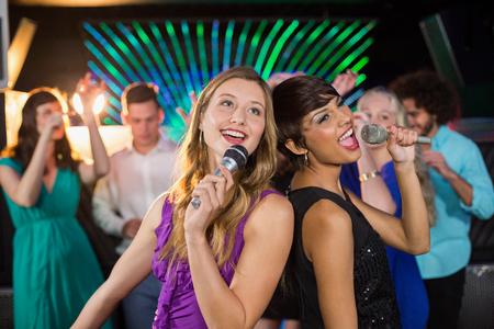Dos mujeres hermosas que se colocan de nuevo a la espalda y cantando canción juntos en la barra de