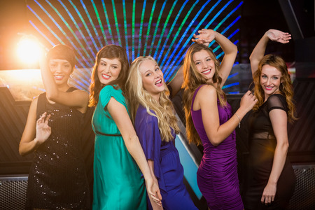 dance bar: Portrait of smiling female friends dancing on dance floor in bar Stock Photo