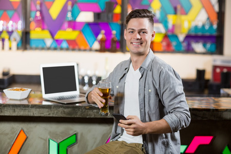 Portrait of smiling man using mobile phone while having glass of beer at bar counter Stock Photo