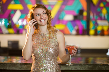 Happy young woman talking on mobile phone while having cocktail at counter