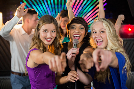 Portrait of smiling female friends singing song together in bar Stock Photo