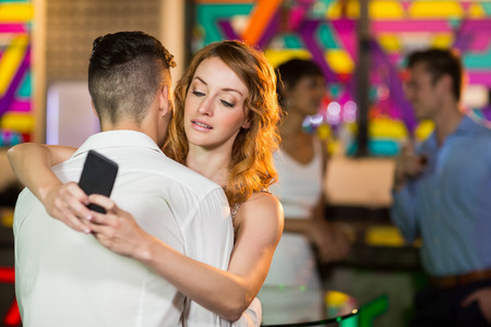 Woman checking her mobile phone while embracing a man in bar Stock Photo