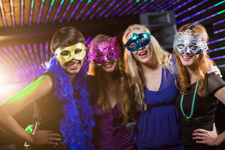 Portrait of smiling female friends wearing masquerade in bar