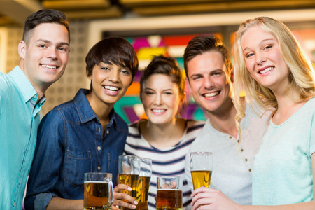 girls night out: Portrait of smiling friends having glass of beer in party at bar Stock Photo