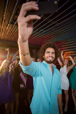 dance bar: Man taking a selfie from mobile phone while friends dancing on dance floor at bar