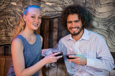 Portrait of smiling couple toasting a glass of wine in bar Stock Photo