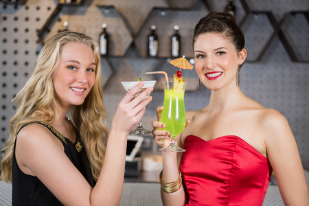 girls night out: Portrait of smiling female friends holding glass of cocktail in bar