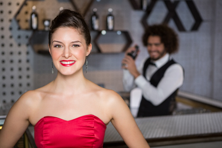 shaking out: Portrait of smiling beautiful woman standing in bar