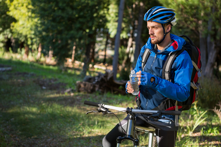 Male mountain holding water bottle standing with bicycle in the forest Stock Photo