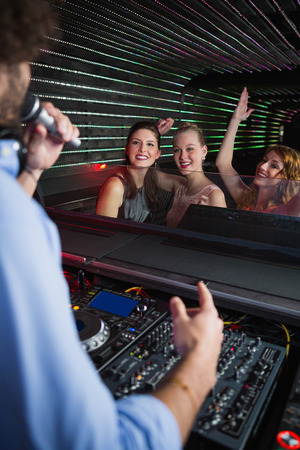 dance bar: Male disc jockey playing music with three women dancing on the dance floor at bar