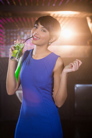 dance bar: Portrait of young woman dancing on dance floor while having cocktail in bar Stock Photo