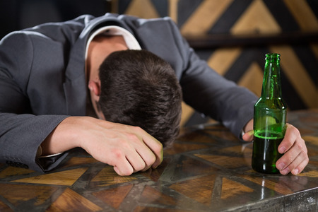 inebriated: Drunk man lying on a counter with bottle of beer at bar Stock Photo