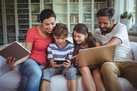 ソファーに坐っている幸せな家族と自宅のラップトップ、携帯電話やデジタル タブレットを使用して
