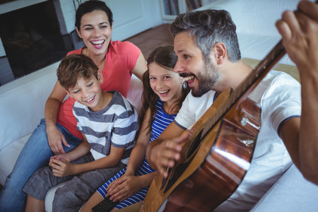 family sofa: Portrait of happy family sitting on sofa with a guitar Stock Photo