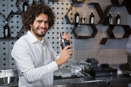 Portrait of happy waiter shaking drink in cocktail shaker in a bar Stock Photo