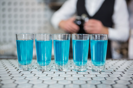 blue lagoon: Glass of blue lagoon drinks on bar counter and bartender standing in background
