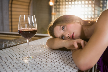 Woman lying on bar counter with wine glass on table in bar