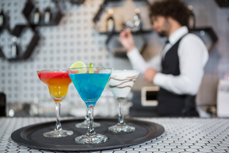 bartending: Various cocktails on a serving tray in bar counter and bartender standing in background Stock Photo