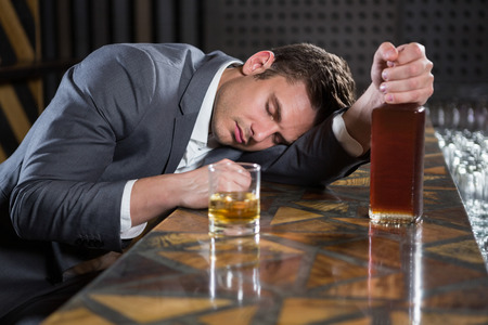 inebriated: Drunk man lying on a counter with bottle of whisky at bar