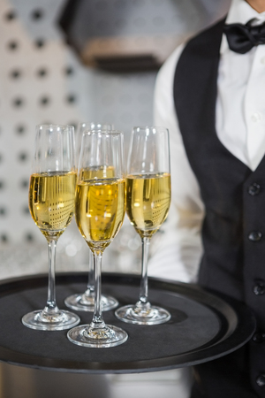 professional flute: Mid section of bartender holding tray of champagne glasses in bar Stock Photo